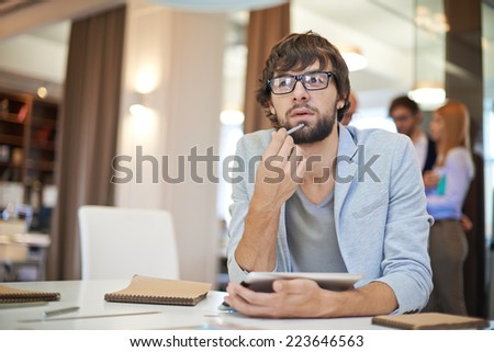 Handsome businessman in casual sitting at workplace on background of his partners - stock photo