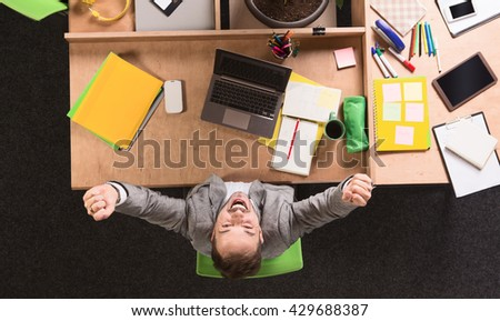 Handsome businessman in grey business suit sitting at table with his arms raised while working in office. Cheerful man expressing happiness. - stock photo