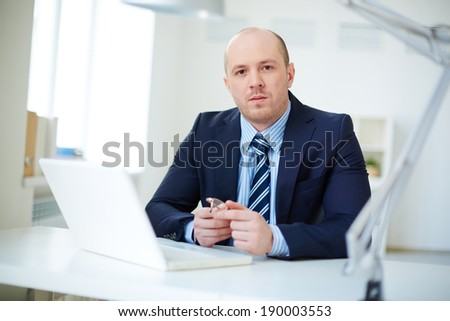Handsome businessman in smart suit looking at camera in office - stock photo