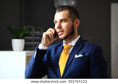 Handsome businessman in suit speaking on the phone in office - stock photo