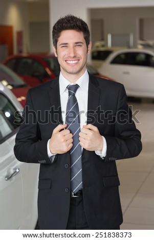 Handsome businessman in suit stading at new car showroom - stock photo