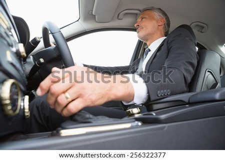 Handsome businessman in the drivers seat in his car - stock photo