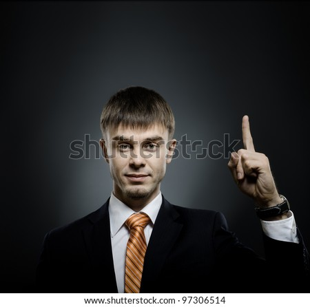 handsome businessman index finger point upwards, on dark grey background - stock photo