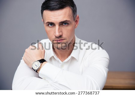 Handsome businessman looking at camera over gray background - stock photo