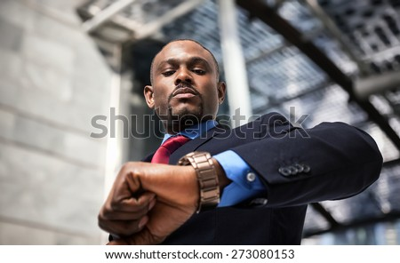 Handsome businessman looking at his watch - stock photo