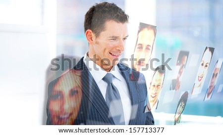 Handsome businessman looking at profile pictures on digital interface - stock photo