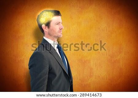 Handsome businessman looking away against orange background - stock photo