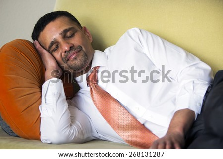 handsome businessman lying on couch and sleeping - stock photo