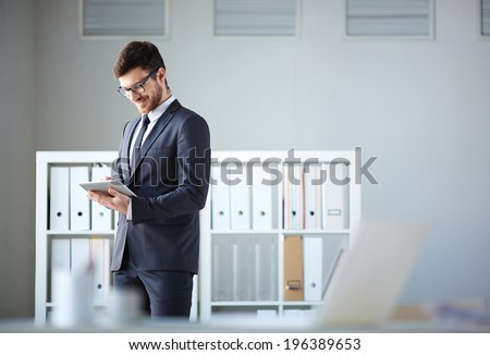 Handsome businessman networking in office - stock photo