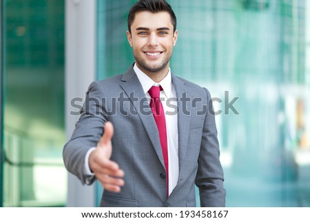 Handsome businessman offering handshake in an urban setting - stock photo