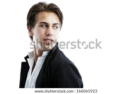 Handsome businessman or playboy in an open necked shirt and stylish jacket looking back over his shoulder at blank white copy space. - stock photo