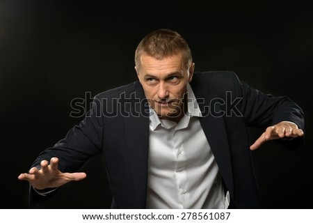 Handsome Businessman posing on a black background - stock photo
