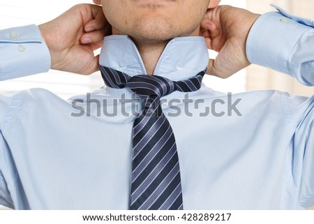 Handsome businessman preparing to official event, straighten tie. New job interview, self motivation for confidence, trying fashionable necktie knot, tailor service concept - stock photo