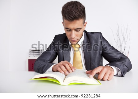 Handsome businessman reading a book in his office - stock photo