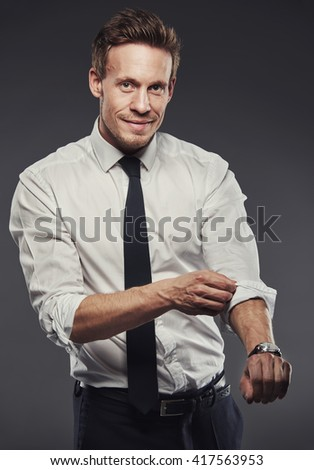 Handsome businessman rolling up his shirt sleeves while looking at the camera with a friendly smile, grey background - stock photo