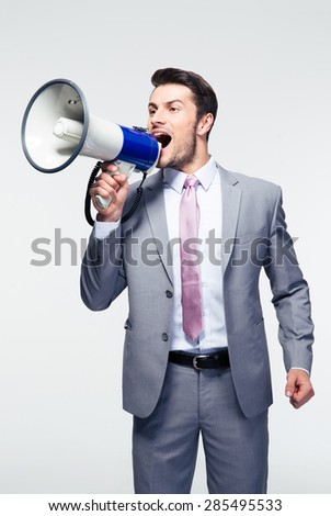 Handsome businessman shouting in loudspeaker over gray background - stock photo