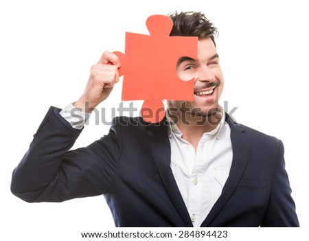 Handsome businessman showing a piece of jigsaw puzzle, over white background. - stock photo