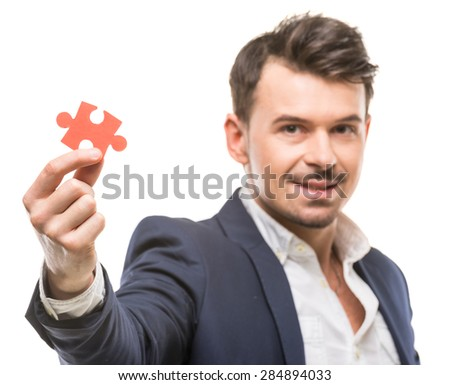Handsome businessman showing small jigsaw puzzle over white background. - stock photo