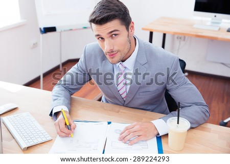 Handsome businessman signing document in office and looking at camera - stock photo