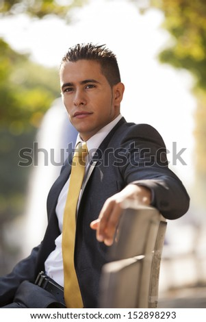 Handsome businessman sited at the bench park - stock photo