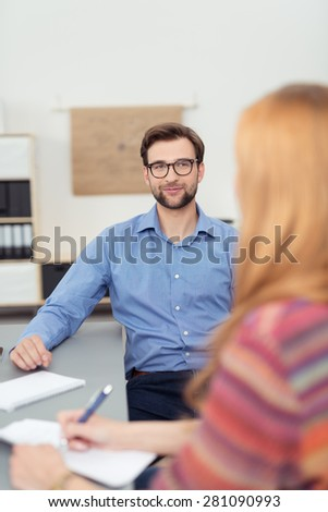 Handsome Businessman, Sitting at the Table Inside the Office, Listening to his Partner While Talking to him. - stock photo