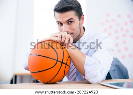 Handsome businessman sitting at the table with ball in office and looking at camera - stock photo