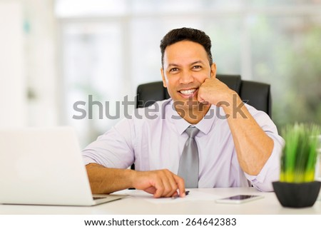 handsome businessman sitting in office looking at the camera - stock photo