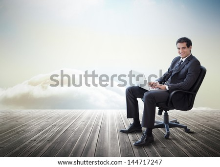 Handsome businessman sitting on a swivel chair and using his laptop on decking with heavenly backdrop - stock photo