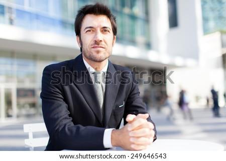 Handsome businessman sitting outdoor - stock photo