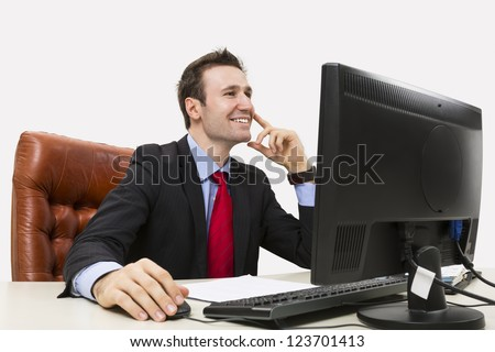 Handsome businessman smiling positively in office while using his computer. - stock photo