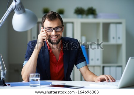 Handsome businessman speaking on the phone and working with laptop in office - stock photo