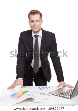 Handsome businessman standing behind the office desk - stock photo
