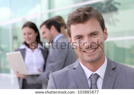 Handsome businessman standing in front of group of people - stock photo