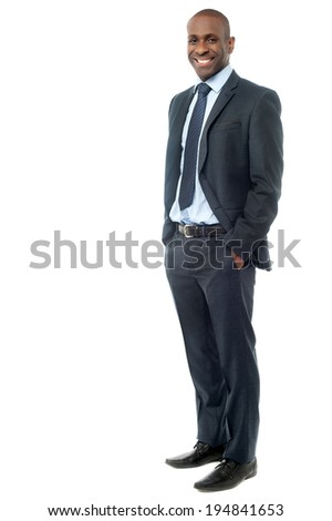 Handsome businessman standing with hands in pocket - stock photo