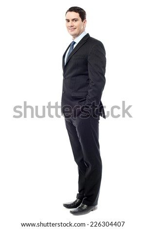 Handsome businessman standing with his hands in pockets - stock photo