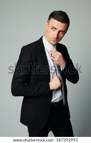 Handsome businessman straightening his tie on gray background - stock photo