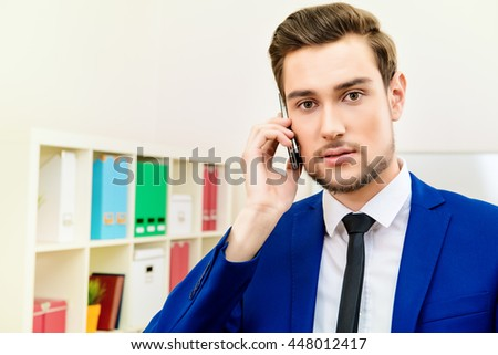 Handsome businessman talking on his cell phone at the office. - stock photo