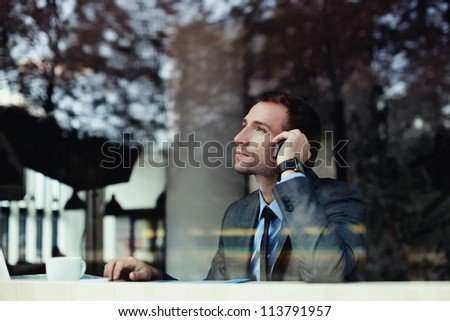 Handsome businessman talking on the phone in coffee shop. - stock photo