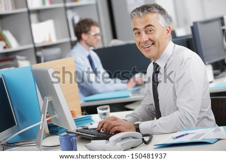 Handsome businessman typing on keyboard at his desk - stock photo