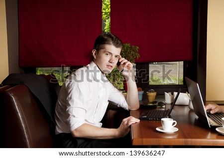 Handsome businessman using a mobile phone and laptor  in cafe. - stock photo