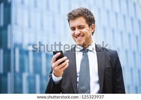 Handsome businessman using a smartphone - stock photo