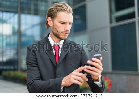 Handsome businessman using his smartphone - stock photo