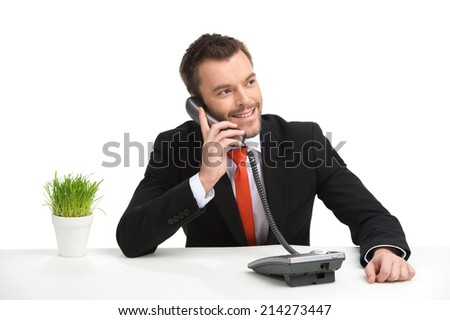 Handsome businessman using landline phone. young guy sitting at table with green grass - stock photo