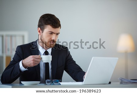 Handsome businessman using laptop and having tea or coffee in office - stock photo