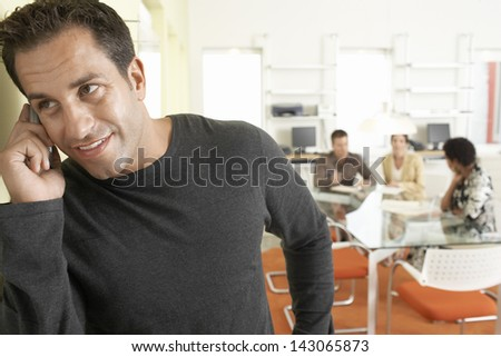 Handsome businessman using mobile phone with colleagues discussing in background - stock photo