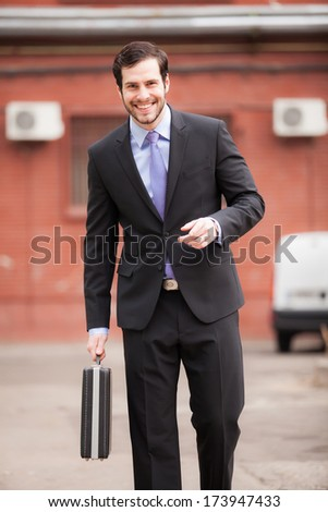 handsome businessman walking with his briefcase in his hand and smiling - stock photo