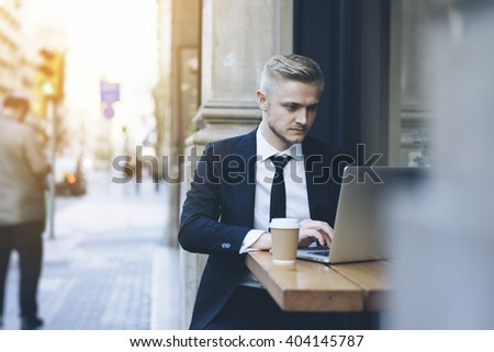 Handsome businessman wearing suit and using modern laptop outdoors, successful manager working in cafe during break and searching information in internet on his notebook computer - stock photo