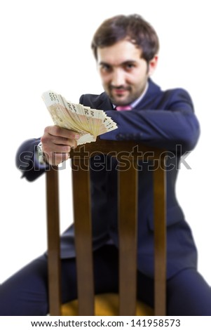 Handsome businessman with a lot of cash, sitting on a chair, isolated on white - stock photo