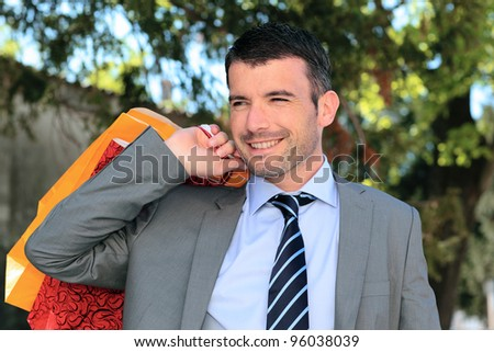 handsome businessman with bags outdoor before christmas - stock photo