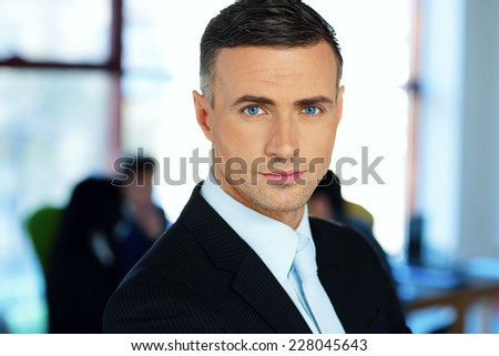 Handsome businessman with colleagues on background - stock photo